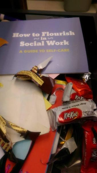 "Desk drawer opened to reveal candy wrappers and a folded paper with ""Guide to Self-Care"""