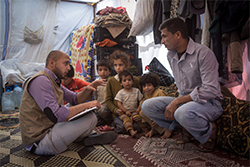 Male social worker kneeling next to fahter and son in a tent in a refugee camp in Lebanon