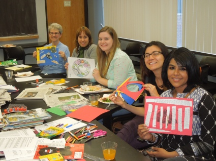 Groups at table holds up the art they have made: cutouts, collages, mandalas