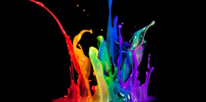 splashes of paint in many colors erupting against a black background