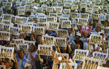 Tokyo: People hold placards denouncing Japan's legislation to abandon decades of pacifism, July 24, 2015.