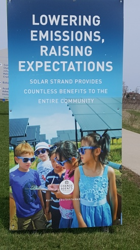 "Sign iwth picture of children in sunglasses in front of the UB solar panels with caption ""Lowering Emissions, Raising Standards, Solar strans provides countless benefits to the entire community"""