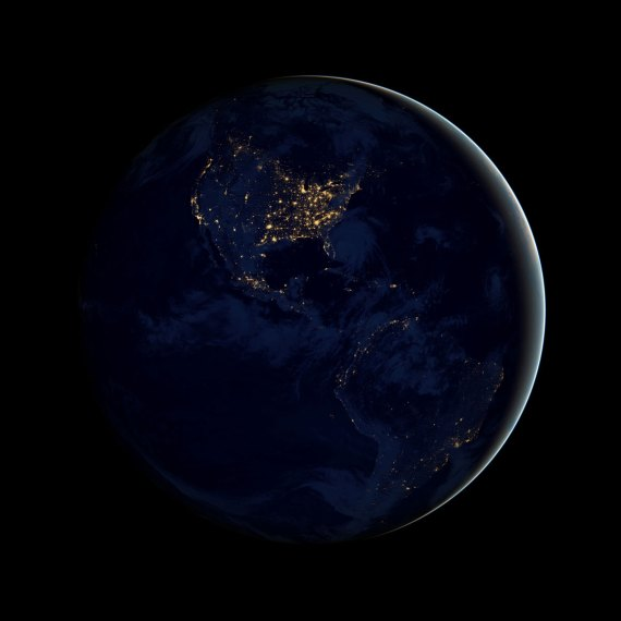Earth as seen from space with North and South America visible and cities shining as points of yellow light on the blue continents