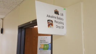 "sign above office door ""UB Alkaline Battery Recycling Drop Off"""