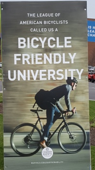 "Banner shows man on bicycle with book bag leaning forward on bike against a campus building background. Text says ""The League of American Bicyclists called us a Bicycle Friendly University"""