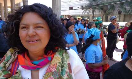 Caceres is shown standing in front of a march of women in blue shirts and kercheifs. She is smiling, weraing a white embroidered blouse and bright colored scarf.