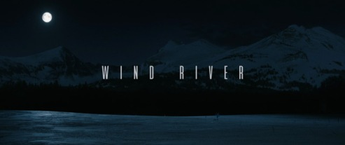 """Movie Title image"""" The words """"Wind River"""" are in teh middle of a rectangular poster, againt background of showy ground under a dark blue night sky"""