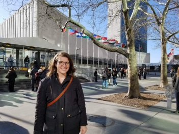Megan Carroll stands in front of the United Nations Building in New York City, She is a white woman, wearing glasses, a big smile and a black winter jacket. Flags from many nations are seen behind her.