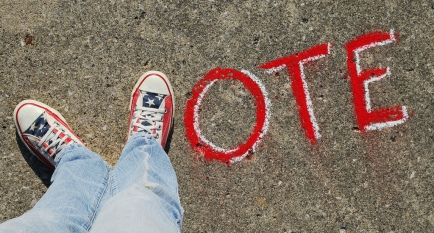 feet in red white blus sneakers form in word VOTE chalked on asphalt