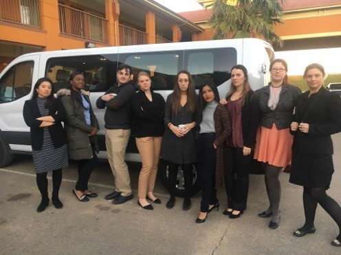 9 of the students stand in front of a van, at the hotel in Dilley.