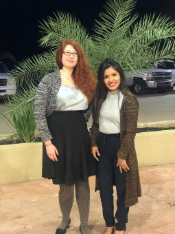 two women stand in front of small palm tree