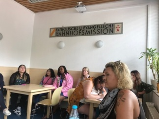 "Our group in a meeting room in Bahnhofsmission. Six young women sit at wooden tables, under a sign, ""Katholique U. Evangelische"" and loot"