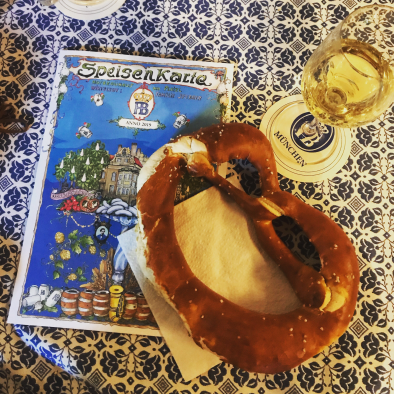 Large soft pretzel and mug of beer on blue and white tablecloth, with place mat from a beer garden in Munich