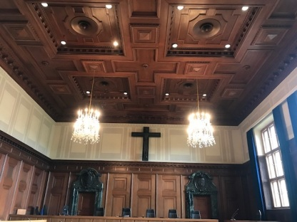 Courtroom at Nuremberg, with wood paneling and coffered ceilings. Two chandeliers are brightly lit, and a cross hangs ont e wall behind the bench with its five chairs.