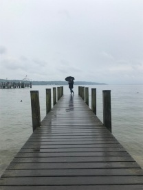 woman stands at end of a pier, wiht water and faint outline of hills behind her.