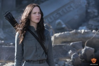 "Katniss Everdeen of the movie, ""The Hunger Games"" is shown standing in awar zone in grey jumpsuit, with quiver of arrows on her back. A crashed plane is in the backgrous, witht the word ""Justice"" on its side.Jennisfer Lawrence is the actor who plays Katniss."