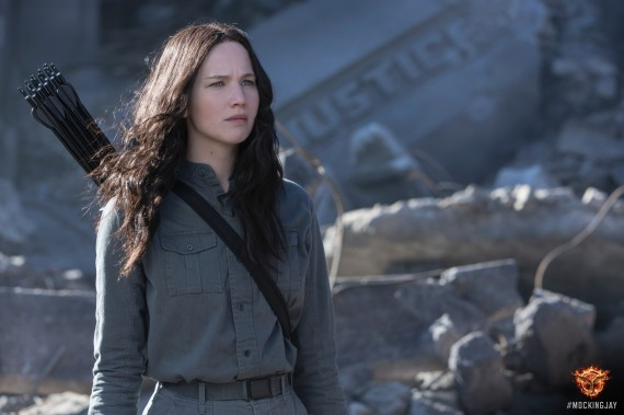 """Katniss Everdeen of the movie, """"The Hunger Games"""" is shown standing in awar zone in grey jumpsuit, with quiver of arrows on her back. A crashed plane is in the backgrous, witht the word """"Justice"""" on its side.Jennisfer Lawrence is the actor who plays Katniss."""