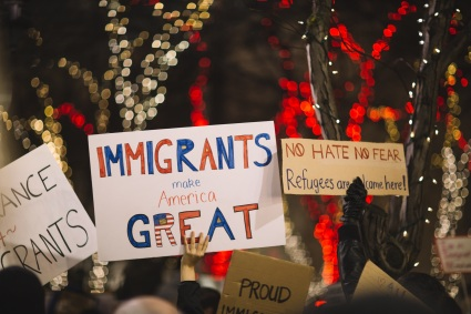 "Signs at a rally for immigrant rights: ""Immigratns make America Great"" in red and blue lettering, ""No Hate No Fear Refugees are Welcome Here."""