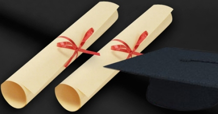 Two rolled graduate certificates tied with red ribbon sit by a black graduation cap (flat a square top with a deep round headpiece..