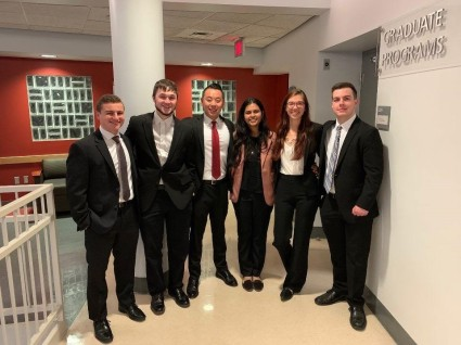 A group of six MBA students, four men and two women. Kelly Zaky is the second from the right.