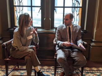 Kristie Bailey seated to the left, is speaking with Senator Tim Kennedy's Chief of Staff Adam Fogel. Both are white; Bailey is dressed in a sweater and slacks and Fogel is in a suit.