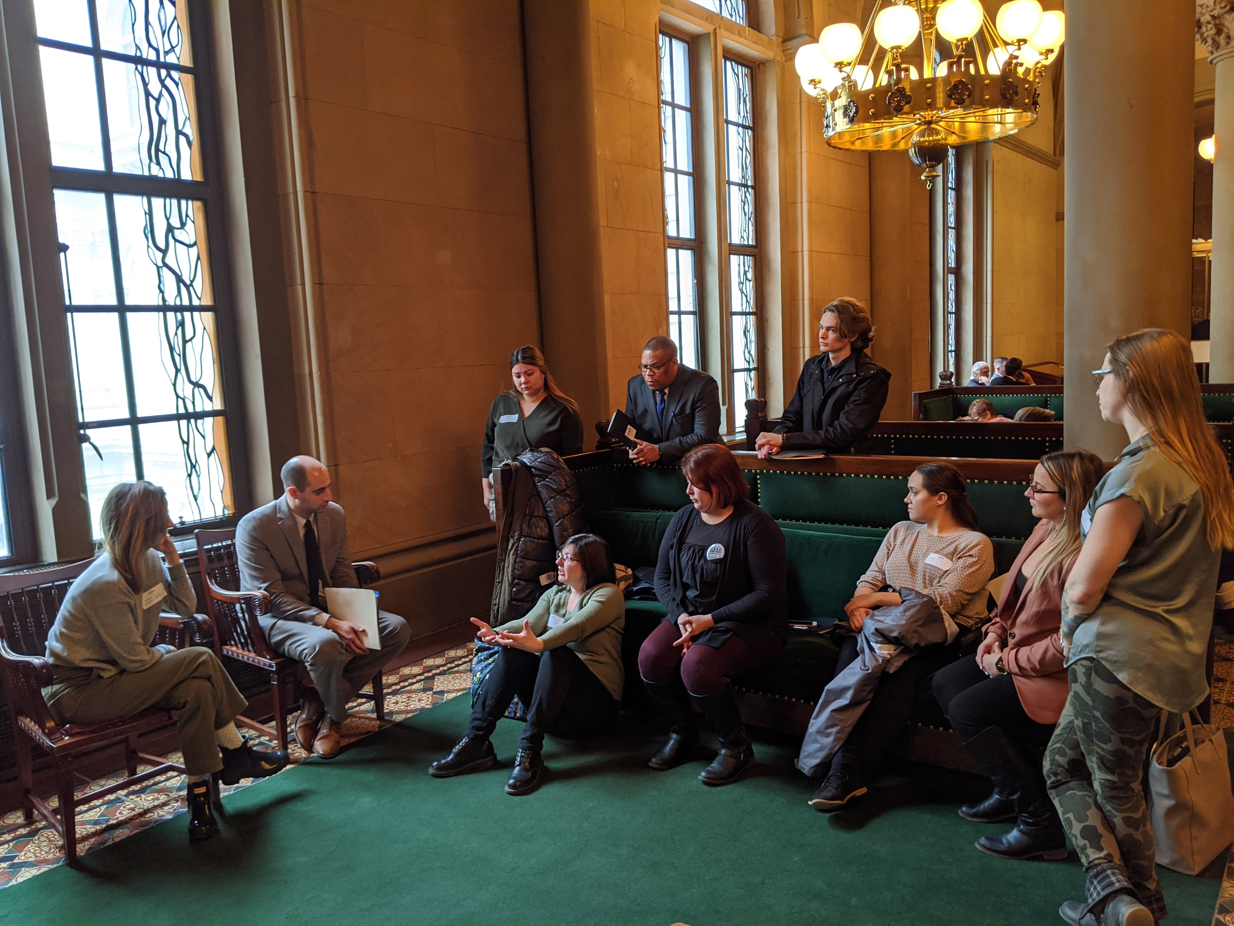 Group is shown in NYS Senate Chamber waiting area. KAt Wilson is seated in front of a couch and is gesturing with her hands as the group listens,
