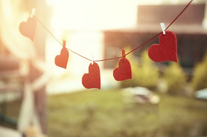Against a blurred sunlit background, a clothesline has red paper heart clipped to the line.